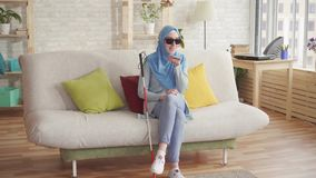 Het mooie blinde Moslimmeisje met een riet in hijab thuis, geniet smartphone van zitting op de laag stock video