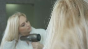 Het mooie blonde in badjas droogt haar met hairdryer stock footage