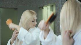 Het mooie blonde in badjas kamt haar haar voor spiegel stock footage