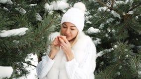 Het mooie blonde eet mandarijn tegen achtergrond van de winterlandschap stock video