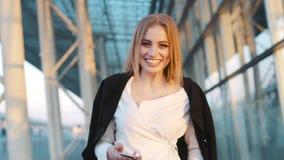 Het mooie blonde Europese meisje lopen door de luchthaventerminal, die haar telefoon met behulp van, kijkt net naar de camera en stock video