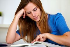 Het mooie blonde jonge meisje bestuderen stock fotografie