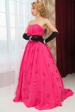 Het mooie blonde in lange rode kleding bevindt zich naast het venster stock foto