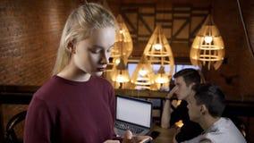 Het mooie blonde maakt vraag terwijl status in koffie stock footage