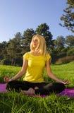 Het mooie blonde mediteert in openlucht in het bos stock afbeelding
