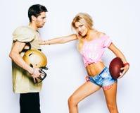 Het mooie blonde meisje cheerleader met een bal valt een strateeg aan Een speler in een voetbal eenvormig met een helm stock foto