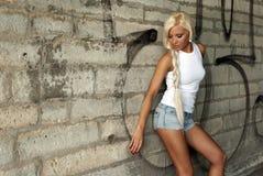 Het mooie blonde meisje stellen door de muur stock fotografie