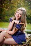 Het mooie blonde meisje stellen in een de herfstbos Stock Afbeeldingen