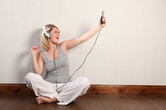 Het mooie blonde meisje zingen aan muziek thuis Stock Fotografie