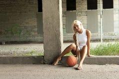 Het mooie blonde meisje zit met basketbal Stock Fotografie