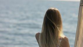 Het mooie blonde ontspannen op een jacht op zee stock video