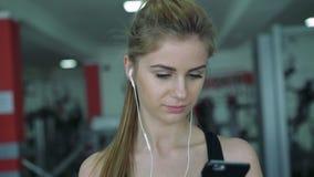 Het mooie blonde op de tredmolen gebruikt de telefoon en het luisteren aan muziek 4K stock video