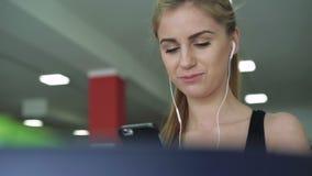 Het mooie blonde op de tredmolen gebruikt de telefoon en het luisteren aan muziek 4K stock videobeelden