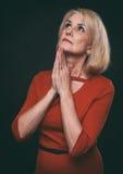 Het mooie blonde oude vrouw bidden Royalty-vrije Stock Afbeelding