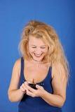 Het mooie blonde overseinen van de vrouwentekst op mobiel Royalty-vrije Stock Fotografie
