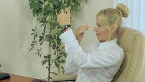 Het mooie blonde poedert haar gezicht binnen op het werk stock video