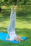 Het mooie blonde preteen meisje in lichte kleding het praktizeren yoga op een mat Gezonde Levensstijl In openlucht training Stock Foto