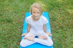 Het mooie blonde preteen meisje in lichte kleding het praktizeren yoga op een mat in het park Gezonde Levensstijl Royalty-vrije Stock Foto's