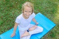 Het mooie blonde preteen meisje in lichte kleding het praktizeren yoga op een mat in het park Gezonde Levensstijl Royalty-vrije Stock Fotografie