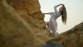 Het mooie blonde stellen onder rotsen in plotseling witte kleding stock videobeelden