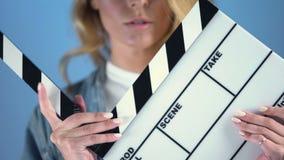 Het mooie blondeactrice stellen voor auditie met de raad van de filmklep, het gieten stock video