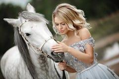 Het mooie blondemeisje in kleding strijkt een grijs paard binnen op aard Royalty-vrije Stock Afbeelding