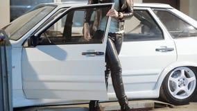 Het mooie blondemeisje in leerbroeken krijgt uit auto stock footage