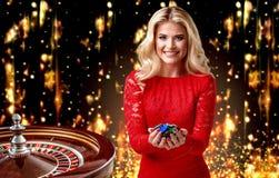 Het mooie blondemeisje met spaanders bevindt zich op de achtergrond van een koninklijke roulette collage met een gokker, roulette royalty-vrije stock foto