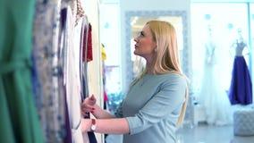 Het mooie blondemeisje modieus selecteren de kleding in de opslag Winkelend wijfje stock videobeelden