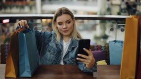 Het mooie blondemeisje neemt selfie op haar telefoonzitting in koffie met het winkelen zakken stock video