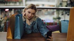Het mooie blondemeisje neemt selfie op haar telefoonzitting in koffie met het winkelen zakken stock footage