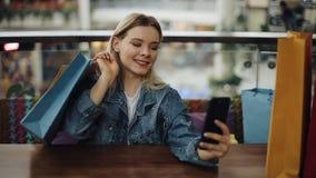 Het mooie blondemeisje neemt selfie op haar telefoonzitting in koffie met het winkelen zakken stock videobeelden