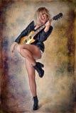Het mooie blondemeisje speelt emotioneel gitaar De textuur van achtergrond is gekrast stock afbeelding