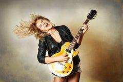 Het mooie blondemeisje speelt emotioneel gitaar De textuur van achtergrond is gekrast royalty-vrije stock fotografie