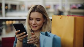 Het mooie blondemeisje typt iets in haar telefoonzitting in koffie met het winkelen zakken stock videobeelden