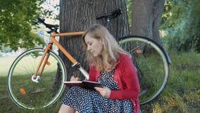 Het mooie blondevrouw ontspannen op gras die in een notitieboekje schrijven Fiets en mooi openbaar park op de achtergrond stock footage