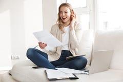 Het mooie blondevrouw stellen die thuis binnen gebruikend laptop computer die door mobiele telefoon spreken zitten stock afbeelding