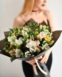 Het mooie boeket van de vrouwengreep van chrysant en rozen bloeit het witte en purpere gelukkige glimlachen op grijs Royalty-vrije Stock Fotografie