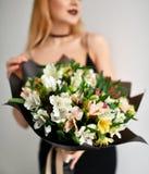 Het mooie boeket van de vrouwengreep van chrysant en rozen bloeit het witte en purpere gelukkige glimlachen op grijs Stock Afbeeldingen