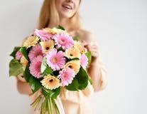 Het mooie boeket van de vrouwengreep van gerbera bloeit het roze en gele gelukkige glimlachen op grijs Royalty-vrije Stock Afbeelding