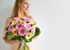 Het mooie boeket van de vrouwengreep van gerbera bloeit het roze en gele gelukkige glimlachen op grijs Royalty-vrije Stock Fotografie
