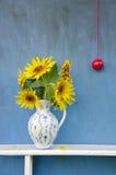 Het mooie boeket van de zomerzonnebloemen in elegante waterkruik met rode appel royalty-vrije stock fotografie