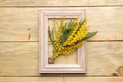 Het mooie boeket van gele mimosa bloeit en een kader op een natuurlijke houten lijst Hoogste mening royalty-vrije stock afbeelding