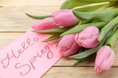 Het mooie boeket van roze tulpenbloemen en de tekst hello springen in notitieboekje op natuurlijke houten achtergrond op De lente stock foto's