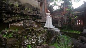 Het mooie bruid stellen dichtbij boeddhistische tempel in Bali Langs het lopen dichtbij Romantisch Huwelijk stock videobeelden