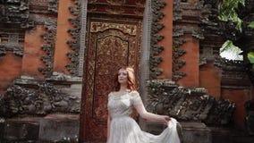 Het mooie bruid stellen dichtbij boeddhistische tempel in Bali Langs het lopen dichtbij Romantisch Huwelijk stock footage