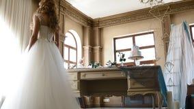 Het mooie bruid stellen dichtbij verfraaide lijst stock videobeelden