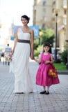 Het mooie bruid stellen samen met flowergirl Stock Foto