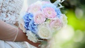 Het mooie bruids boeket in handen van jonge bruid kleedde zich in witte huwelijkskleding stock videobeelden