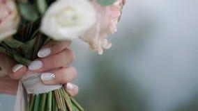 Het mooie bruids boeket in handen van jonge bruid kleedde zich in witte huwelijkskleding Sluit omhoog van grote bos van vers wit stock video